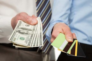 Businessmen holding credit card and money - closeup shot
