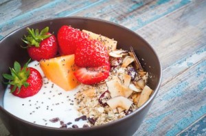 A bowl of healthy breakfast muesli with yogurt and topped with f