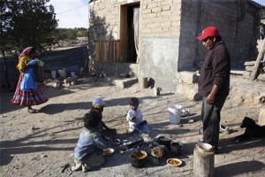 "Raramuri indian Juan Rodriguez, right, of the Tarahumara Mountains watches as his children eat in the town of Huisarorare, northern Mexico, Thursday Jan. 19, 2012. A severe drought has thrown many indigenous communities in the region under severe stress and the Mexican Red Cross has declared the situation ""a food emergency."" (AP Photo/Raymundo Ruiz)"