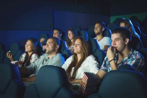 People watching movie in cinema. Selected focus on boy in the first row on the right side