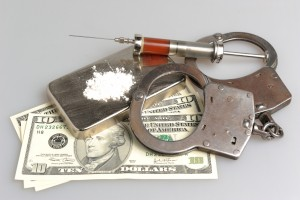 Drugs, syringe with blood, handcuffs and money on gray background