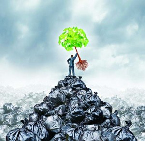 Green businessman concept as a man on top of a mountain heap of garbage holding up a green leaf tree with roots as an environment and conservation icon for waste management or a new healthy beginning.