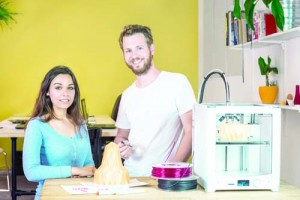 Two product designers, standing behind a table with a 3D Printing machine, discussing a new product and new technologies