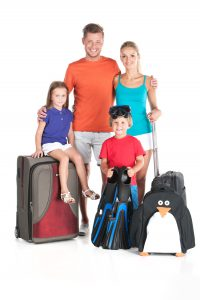 happy family standing with luggage on white background. man hugging woman and holding baby