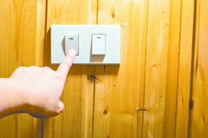 Finger press on light switch button at wooden wall