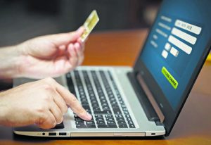 Man holding credit card and entering card numnber to complete purchase