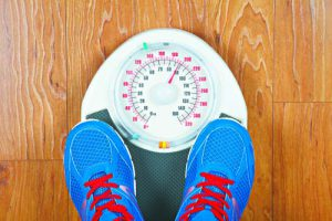 Closeup of man's feet on weight scale indicating overweight