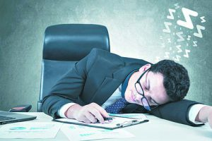Tired male entrepreneur sleeping on desk with paperwork at workplace