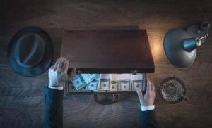 Vintage rich businessman's desk holding a briefcase filled with dollar packs, top view