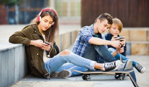 Smiling cheerful teens playing on smarthphones and listening to music
