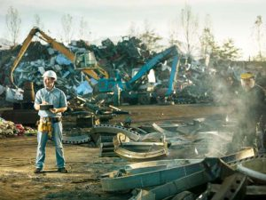 caucasian engineer standing at scrap metal recycling site, inspecting work