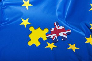 Brexit - Detail of Silky Flag of Blue European Union EU Flag Drapery With Puzzle Piece With Great Britain