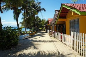 Sandy path along the sea with bungalows