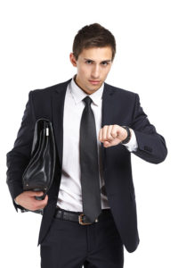 Half-length portrait of businessman handing briefcase and looking at his watch, isolated on white. Concept of business and success
