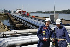fuel pipelines leading to ships with two refinery workers in for