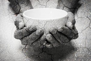 Double exposure hunger begging hands and dry soil