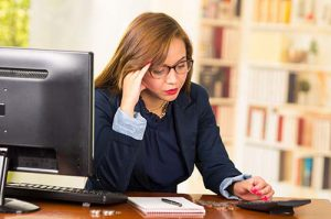 Business woman wearing glasses sitting by desk with computer expressing mild frustration