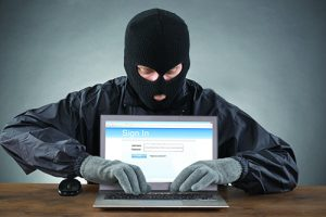 Hacker Hacking Account Of Social Networking Site On Laptop At Desk